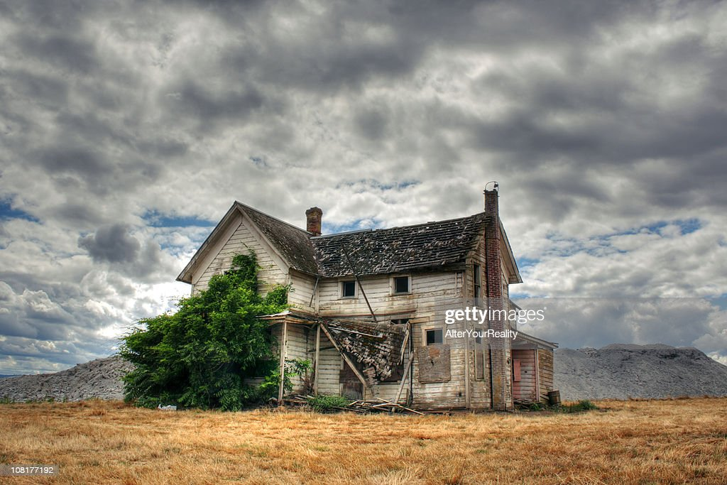 Lone Abandoned And Derelict House In Field With Overcast Sky Stock Photo