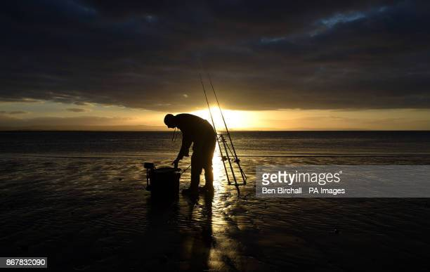 A lone angler on the beach at BurnhamonSea Somerset as the sun sets an hour earlier after the clocks went back one hour last night due to the end of...
