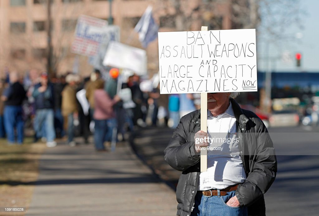 A lone anti-gun activist protests as Second Amendment demonstrators rally on January 9, 2013 at the Colorado State Capitol in Denver, Colorado. Lawmakers are calling for tougher gun legislation after recent mass shootings at an Aurora, Colorado movie theater and at Sandy Hook Elementary School in Newtown, Connecticut.
