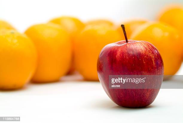 Lone apple standing in front of several blurred oranges