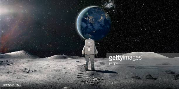 lone astronaut in spacesuit standing on the moon looking at the distant earth - space and astronomy stock pictures, royalty-free photos & images