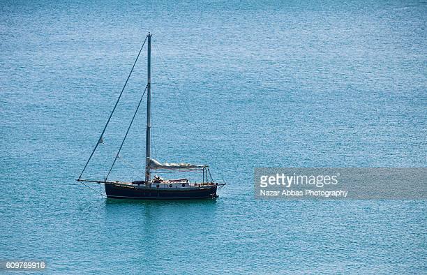 lone boat in calm blue sea against sky - nazar stock photos and pictures
