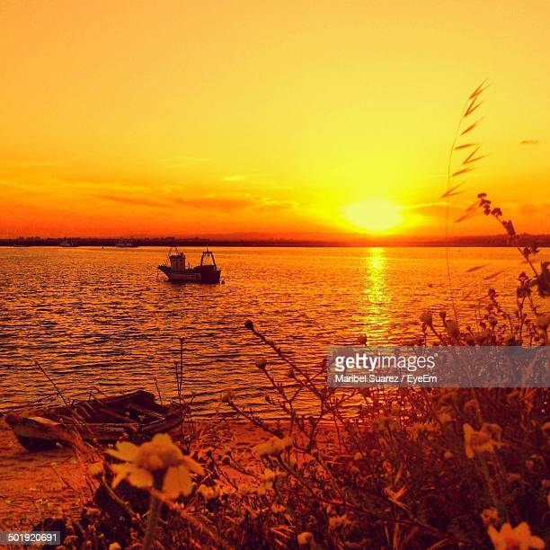 lone boat in calm sea at sunset - suarez stock pictures, royalty-free photos & images