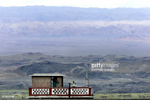 A lone border patrol officer peers through his binoculars from his border outpost 18 August 2000 at Alshanko Pass a key border crossing between...