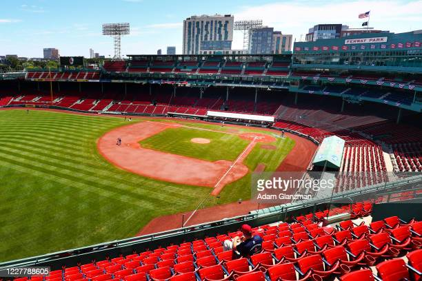 Lone Boston Red Sox employee eats a hot dog in the stands before a game between the Boston Red Sox and the Baltimore Orioles at Fenway Park on July...