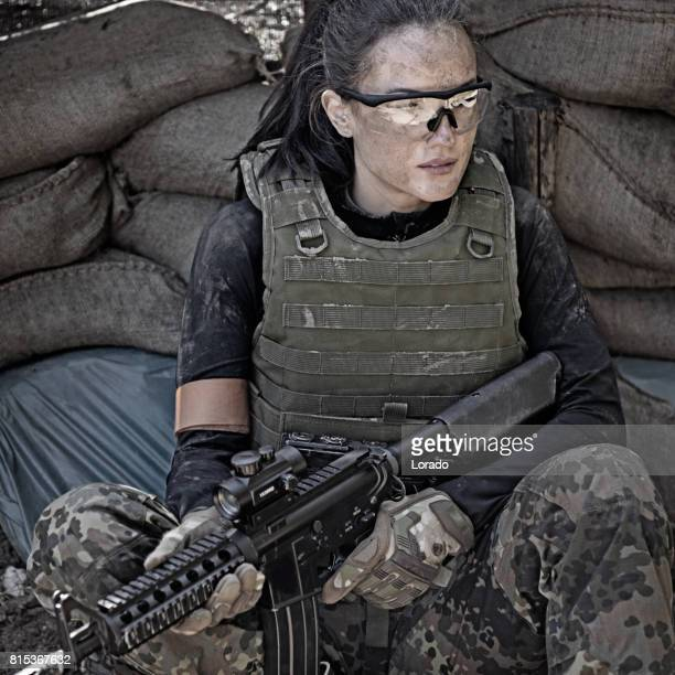 Lone brunette female soldier in outdoor setting