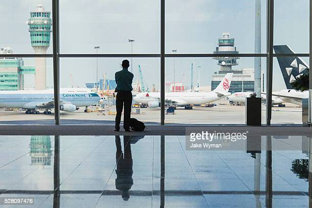 A lone businessman standing at a window in the Hong Kong International Airport