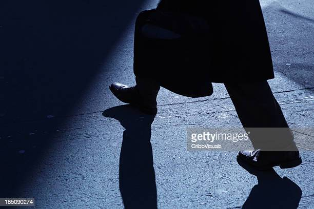 lone businessman walking into blue night shadows - ominous stock photos and pictures