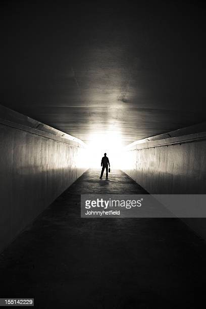 lone businessman walking through tunnel with briefcase - light at the end of the tunnel stock pictures, royalty-free photos & images