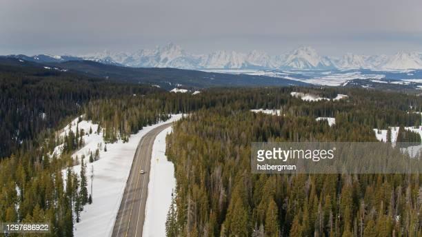 グランドテトンに向かって運転する孤独な車 - 空中 - グランドティトン国立公園 ストックフォトと画像
