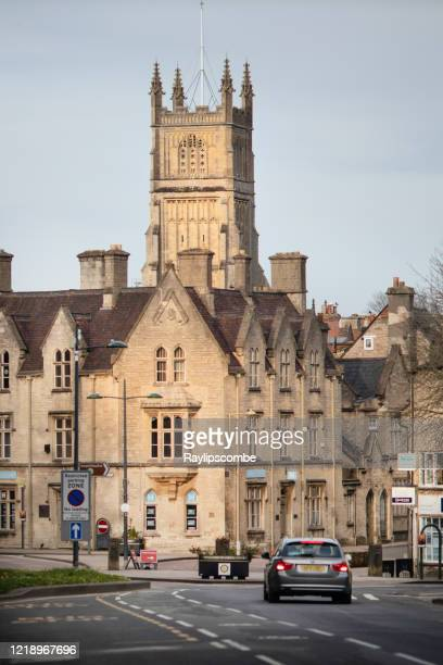 lone car heading towards the town centre of cirencester with a sunlit cirencester parish church in the distance. - cirencester stock pictures, royalty-free photos & images