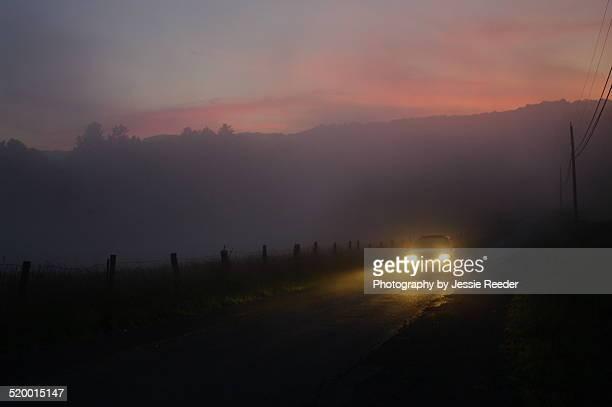 Lone car headlights at night in the fog