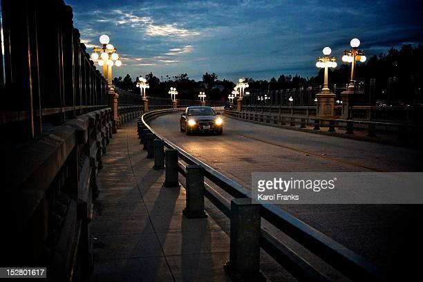 Lone car on night drive on curved bridge