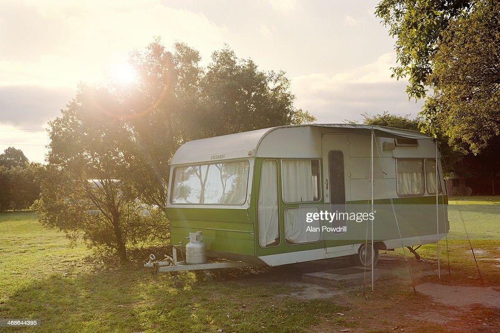 Lone caravan in field, sun behind : Stock Photo