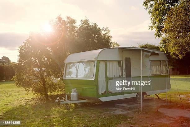 Lone caravan in field, sun behind