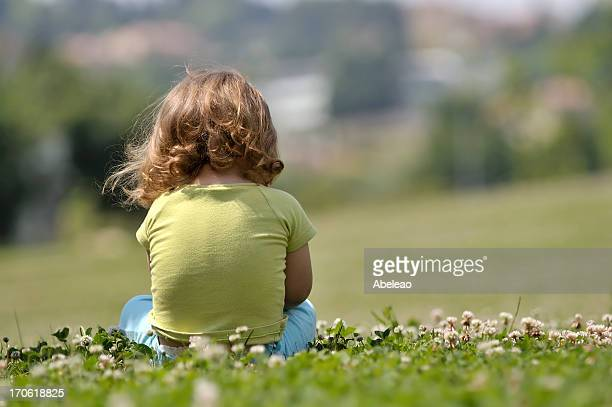 Lone child sitting in field of flowers