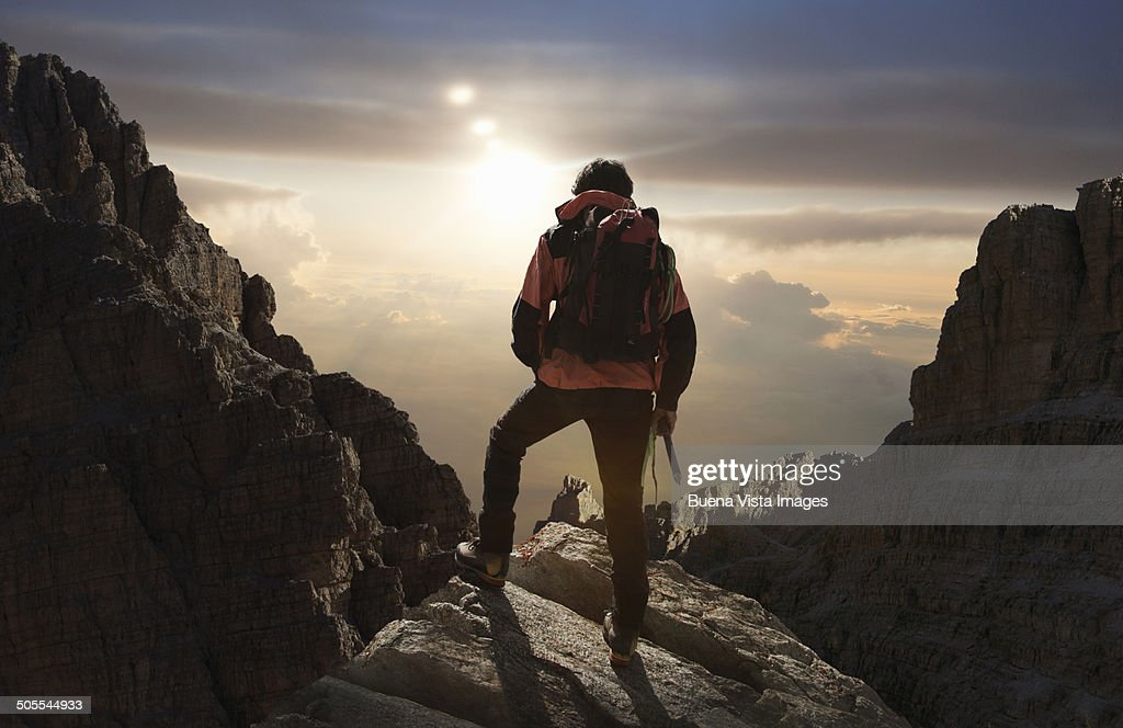 Lone climber on a mountain at sunrise : Stock Photo