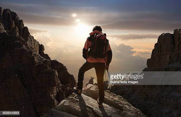 lone climber on a mountain at sunrise - mountaineering stock pictures, royalty-free photos & images