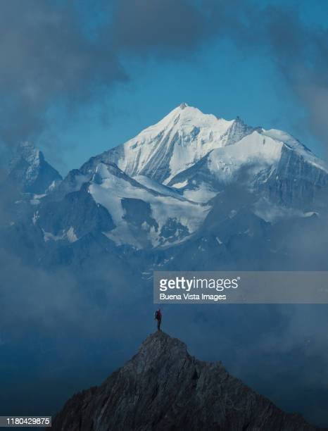 lone climber on a mountain peak - summit stock pictures, royalty-free photos & images