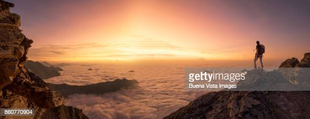 lone climber on a mountain top at dawn - majestic stock pictures, royalty-free photos & images