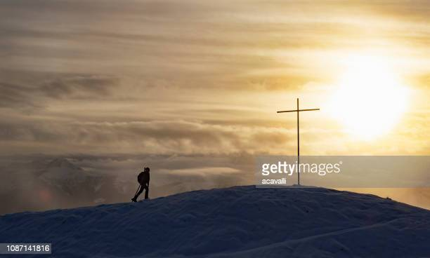 lone climber on a snowy ridge. - cross shape stock pictures, royalty-free photos & images