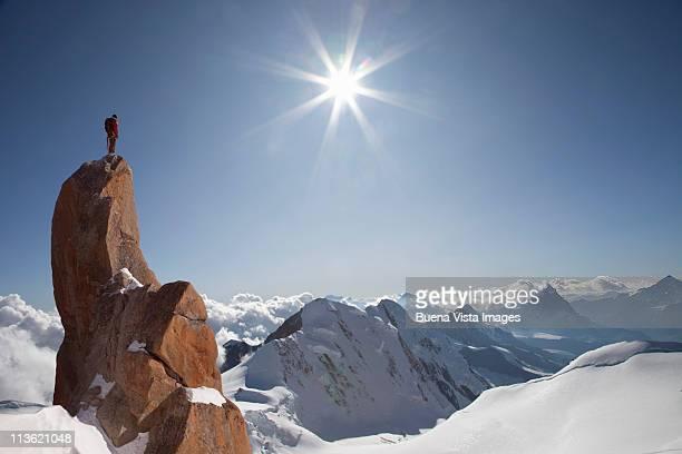 lone climber on top of a peak - spitze stock-fotos und bilder