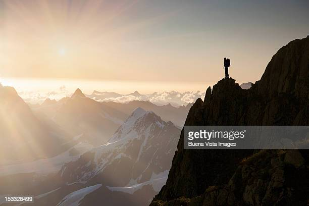 lone climber on top of a peak - bergpiek stockfoto's en -beelden