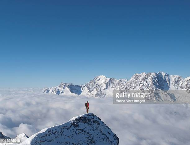 lone climber on top of a snowy peak - bergpiek stockfoto's en -beelden