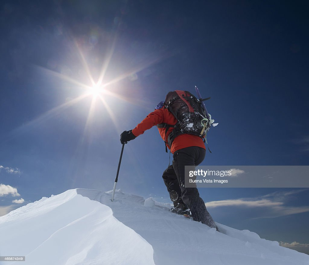 Lone climber reaching a mountain top : ストックフォト