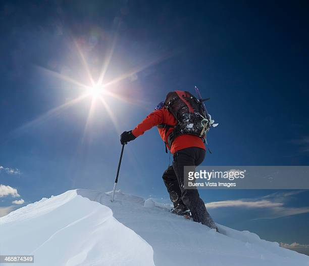 Lone climber reaching a mountain top