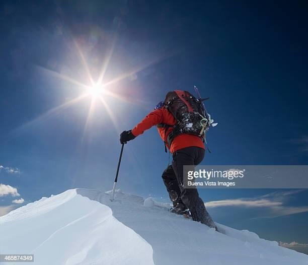 Lone climber reaching a mountain top