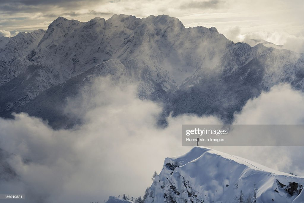 Lone climber standing on a snowy peak : Stock Photo