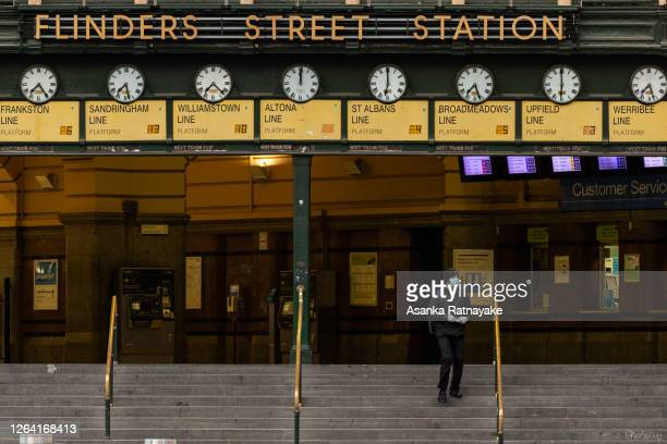 A lone commuter walks out of Flinders Street station on August 06 2020 in Melbourne Australia Retail stores across Melbourne are closed to customers...