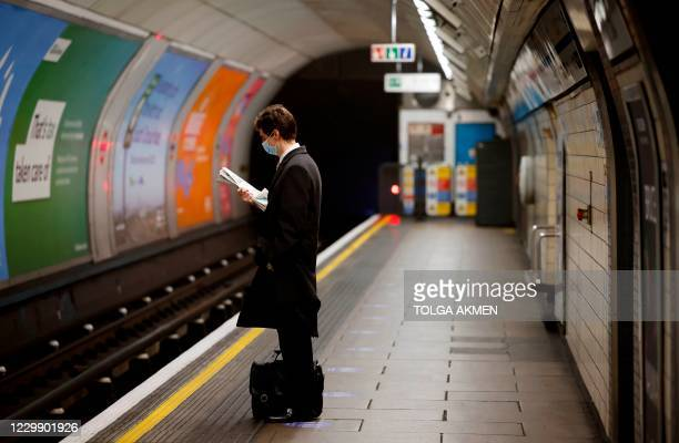 Lone commuter wearing a face mask or covering due to the COVID-19 pandemic, waits on a platform to travel via a London Underground tube train during...