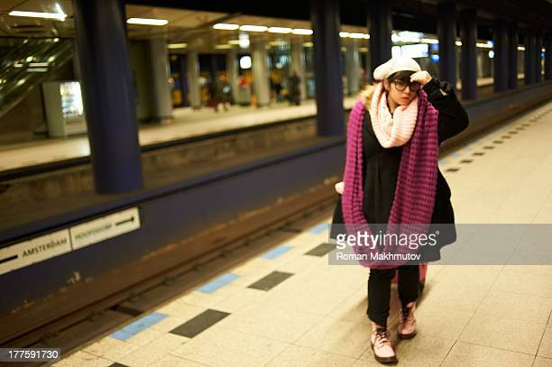 CONTENT] Lone confused and seems lost passenger on empty train station She wears long designer scarf and coat