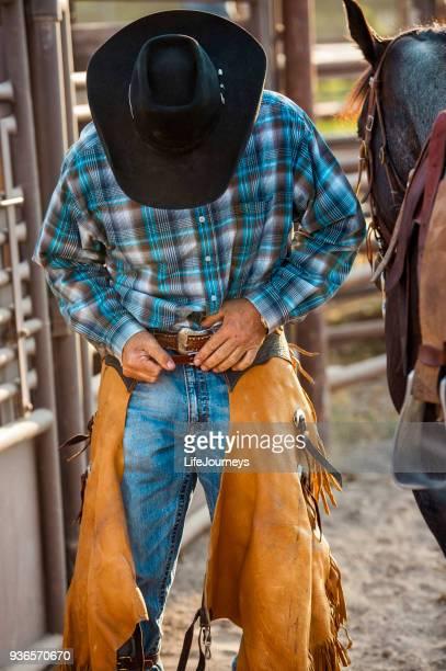 vaquero solitario detrás de las canaletas en un rodeo prepara para montar su caballo de flejado en sus grietas - pantalón de cuero fotografías e imágenes de stock