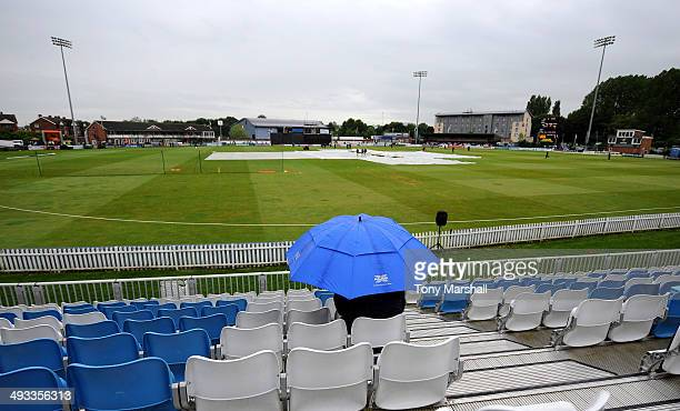 A lone cricket fan sits under an umbrella as the rain comes down at The County Ground during the NatWest T20 Blast match between Derbyshire Falcons...