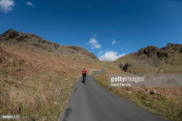 A lone cyclist climbs Hardknott Pass in the English Lake District, UK.