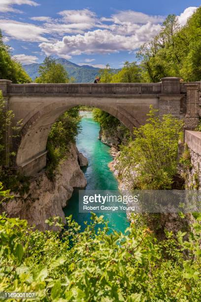 a lone cyclist crosses the napoleon bridge over the soča river - gorizia stock pictures, royalty-free photos & images