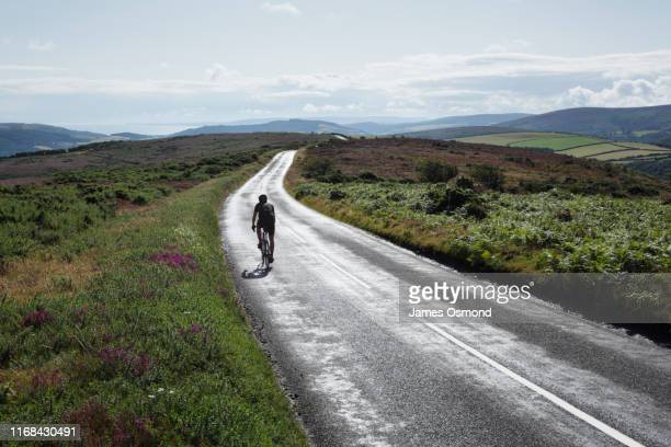 lone cyclist on open road cycling across moorland into the distance. - man made space stock pictures, royalty-free photos & images