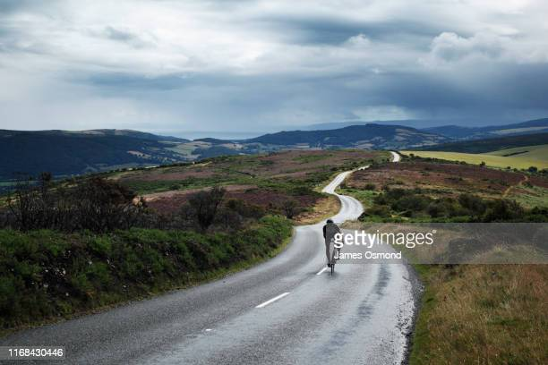 lone cyclist on winding road - bicycle stock pictures, royalty-free photos & images