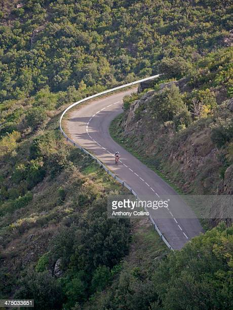 lone cyclist riding a costa brava hill - girona stock photos and pictures