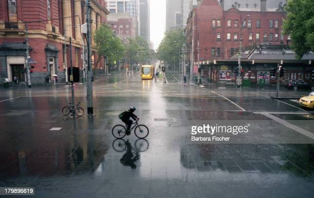 Lone cyclist riding in the rain outside Southern Cross station in Melbourne, Australia. Image from 2010.