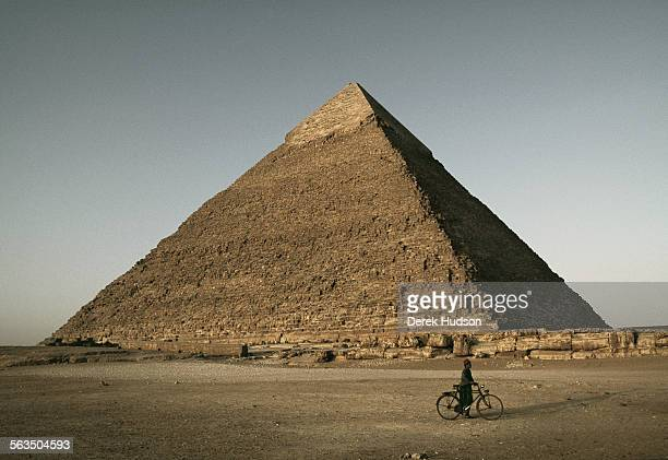 A lone cyclist walks in front of the second largest pyramid Khafre at dusk