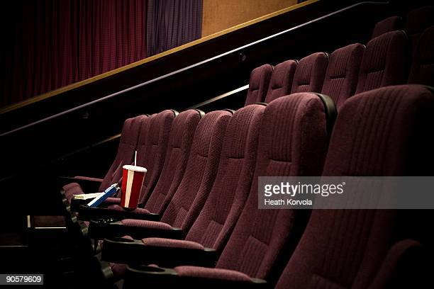 Lone drink + candy in empty theater.