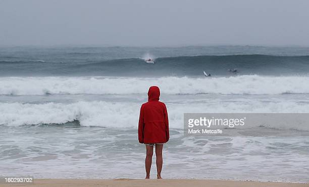 A lone early morning walker watches surfers on Bondi Beach after winds and rain battered Sydney last night on January 29 2013 in Sydney Australia...
