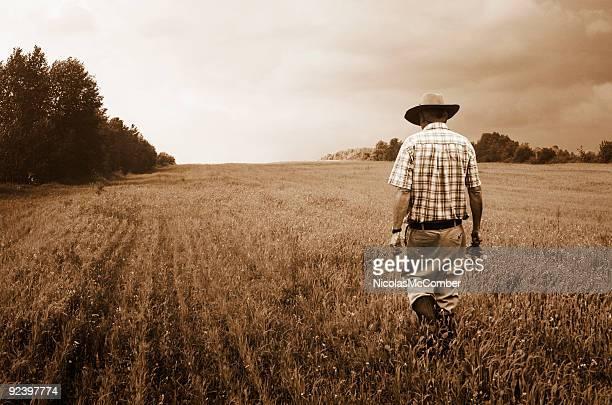 Lone agricultor caminha na sua misty campo Sépia