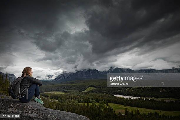 Lone female traveller overlooking stormy landscape