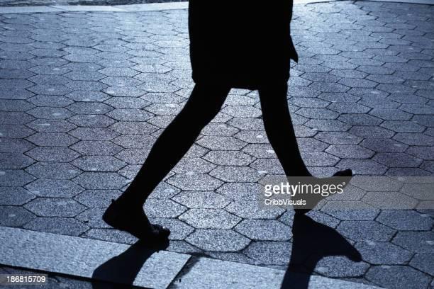 Lone female walking in blue night shadows