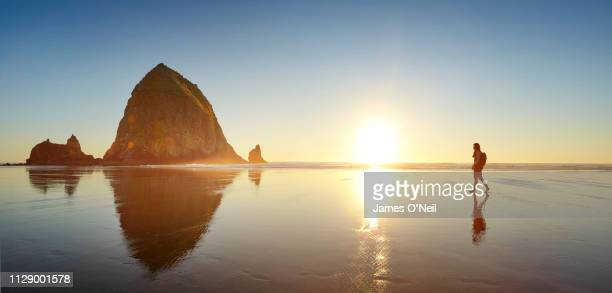 lone female walking towards haystack rock on cannon beach at sunset - panorâmica - fotografias e filmes do acervo